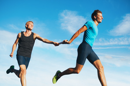 Portrait of young athletes pass the baton in a track relay against sky. Young runner practicing a relay race. Stock Photo