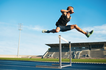Professional male track and field athlete during obstacle race. Young athlete jumping over a hurdle during training on racetrack in athletics stadium. Stock Photo