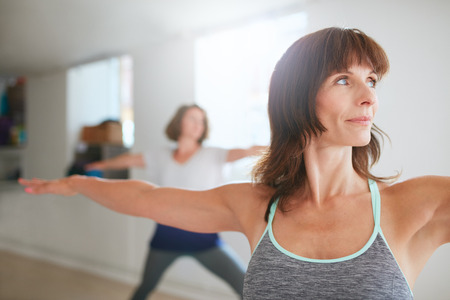 Portrait of beautiful young woman doing the warrior pose during yoga class. Yoga instructor performing Virabhadrasana position in gym. Stockfoto