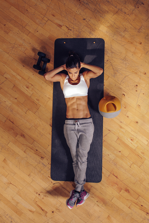 laying on back: Fit young woman lying on exercise mat doing stomach exercises. Overhead view of female working out at the gym