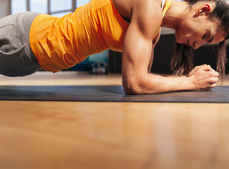 woman close up: Cropped shot of woman exercising in the gym. Muscular female doing core workout on fitness mat with copy space.