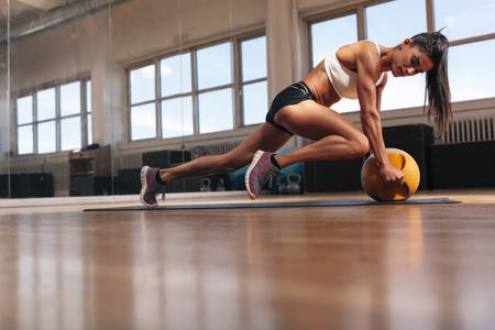musculoso: Mujer que hace ejercicio básico intensa en la estera de fitness. Mujer joven muscular que hace entrenamiento en el gimnasio.