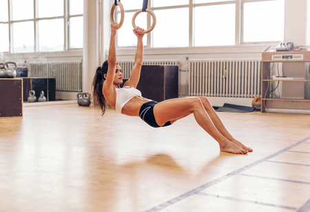 pullups: Muscular young woman doing pull-ups on rings. Fit young female athlete exercising with gymnastic rings at gym.