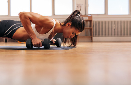 female hand: Strong young woman doing push-ups on dumbbells in gym. Fit female exercising in health club with copy space. Stock Photo