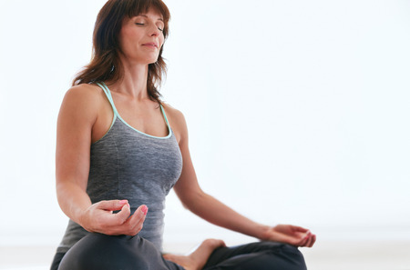 padmasana: Portrait of fit woman sitting in lotus pose meditating. Female trainer practicing Padmasana at gym.
