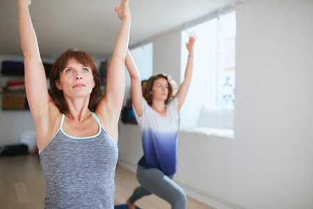 yoga class: Two women practicing yoga forms and positions in gym. Fitness females doing warrior pose at yoga class. Virabhadrasana posture in training session.
