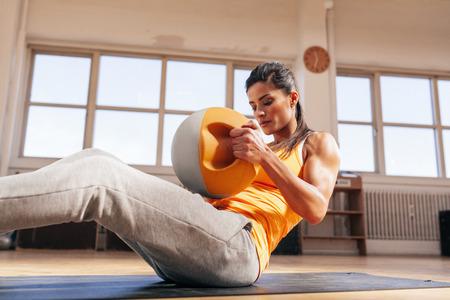 musculoso: Mujer joven de la aptitud que ejercita con la campana hervidor de agua. Mujer joven muscular en ropa deportiva haciendo entrenamiento crossfit en el gimnasio.