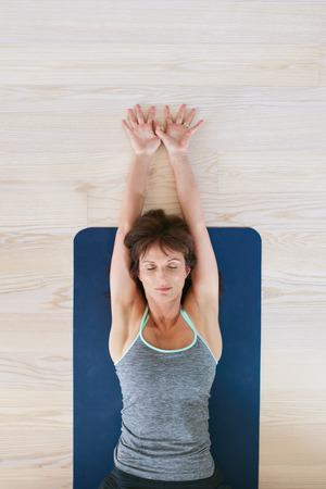 Top view of woman lying on floor with her eyes closed and stretched arms. Fitness woman exercising on yoga mat.