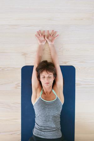 stretching: Vista superior de la mujer tendida en el suelo con los ojos cerrados y estir� los brazos. Mujer de la aptitud que ejercita en la estera de yoga.