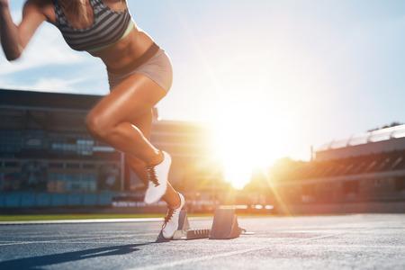Recortar foto de la hembra joven atleta que lanza de la línea de salida en una carrera. Corredor femenino comenzó el sprint de la línea de salida con la luz del sol brillante.