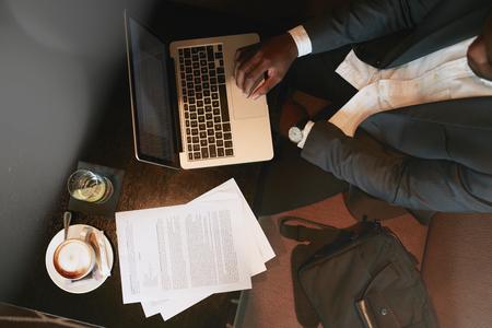 Bovenaanzicht van de zakenman zit bij coffee shop werken op laptop computer. Koffie, water en documenten op tafel.