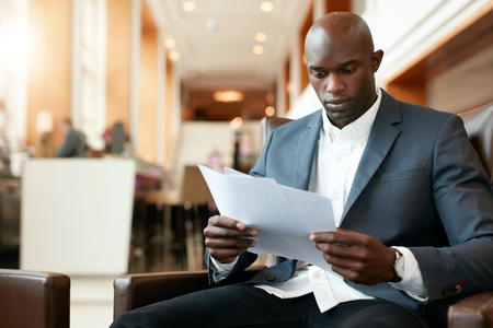 black professional: Portrait of young african businessman sitting at hotel lobby reading documents. Business executive going through paperwork. Stock Photo