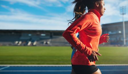 맞는 젊은 여자 실행의 측면보기. 육상 경기장에서 레이스 트랙에 아프리카 여성 운동 선수의 훈련.