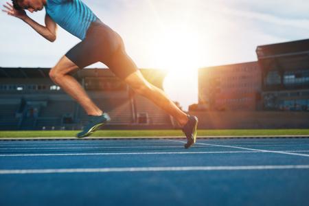 Disparo de joven atleta masculino que lanza de la línea de salida en una carrera. Corredor que se ejecuta en pista de carreras en el estadio de atletismo.
