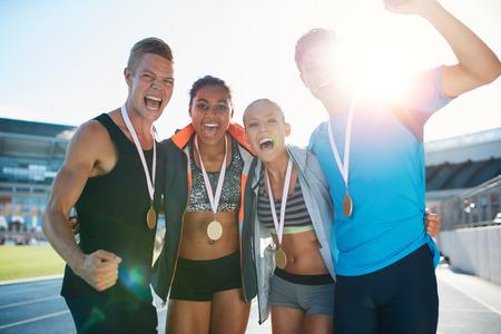 pista de atletismo: Retrato de corredores jóvenes de éxtasis con medallas celebrando el éxito en el atletismo del estadio. Hombres y mujeres jóvenes buscando emocionado después ganador una carrera a pie. Foto de archivo