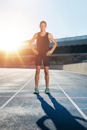 deportistas: Tiro integral de atleta profesional masculino de pie con las manos en las caderas mirando con confianza a la cámara. Sprinter en pista de carreras en el estadio de atletismo con la flama del sol.
