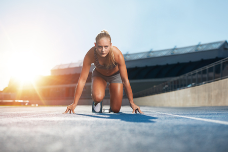 Confident young female athlete in starting position ready to start a sprint. Woman sprinter ready for a run on racetrack with sun flare.
