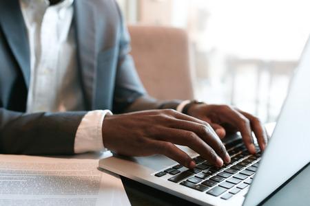 klawiatura: Biznesmen pracuje na laptopie z niektórych dokumentów na stole. Zamknąć na męskich dłoni pisania na klawiaturze laptopa.