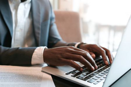 internet keyboard: Businessman working on laptop with some documents on table. Close up on male hands typing on laptop keyboard.