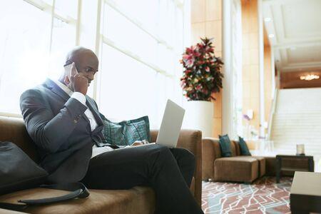 persona sentada: Hombre de negocios sentado en el sofá de trabajo utilizando el teléfono celular y la computadora portátil. Ejecutivo de sexo masculino africana esperando en el vestíbulo del hotel. Foto de archivo