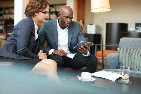 Zakenman blijkt rapporten zakenvrouw op digitale tablet. Mensen uit het bedrijfsleven bijeen in een coffeeshop.