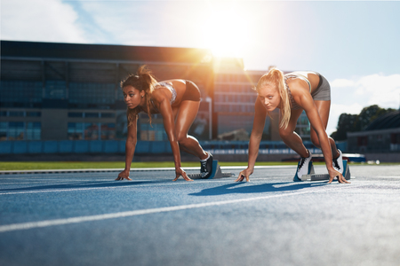 starting position: Two female athletes at starting position ready to start a race. Sprinters ready for race on racetrack with sun flare. Stock Photo