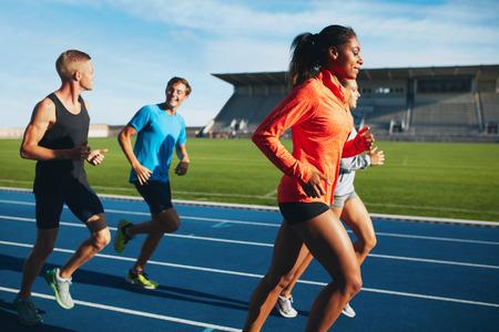 hombres corriendo: Hombres y mujeres aptos que se ejecutan en una pista de carreras. Atletas multirraciales que practican en pista de carreras en el estadio. Foto de archivo