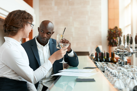 celebratory event: Two young business people toasting drinks at cafe. African businessman with caucasian female partner having a glass of drink at bar after work. Stock Photo