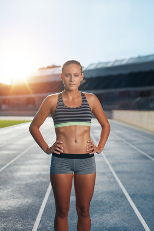 sun track: Fit young woman after run on stadium race track. Confident female athlete standing with her hands on hips looking at camera with sun flare.