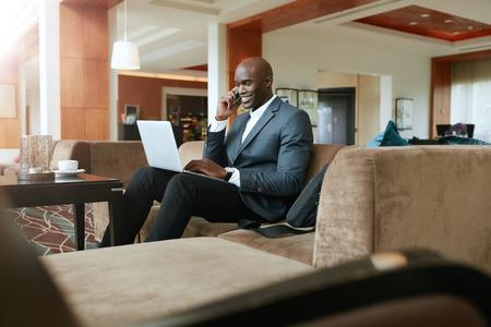 携帯電話とノート パソコンを使用してソファの作業の上に座って幸せな青年実業家。アフリカの男性幹部は、ホテルのロビーで待っています。