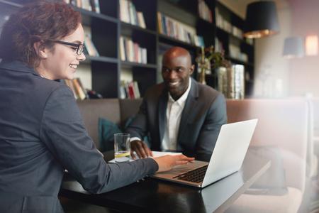 Jeune femme d'affaires montrant présentation sur ordinateur portable à son partenaire d'affaires. Cadres heureux dans une réunion au restaurant Banque d'images - 48290478