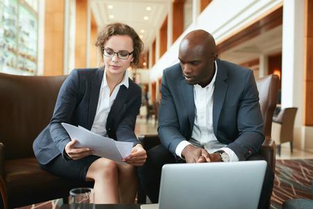 論文の議論のホテルのロビーに座っている男の人と若いビジネス女性の肖像画。ビジネスの人々 は、ドキュメントを読んでコーヒー ショップで会議します。 写真素材 - 48290489