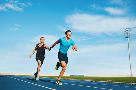 Shot of professional male athletes passing over the baton while running on the track. Athletes practicing relay race on racetrack.