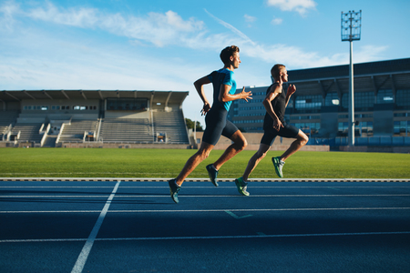athletic: Two young men running on race track. Male professional athletes running on athletics race track.