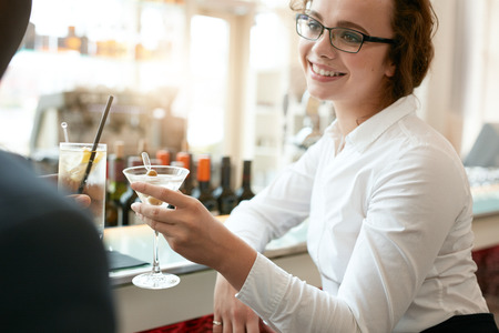 drinks after work: Young business woman toasting drinks with colleague at cafe. Caucasian businesswoman with partner having a glass of drink at bar after work. Stock Photo