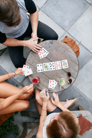 outdoor activities: Three young friends playing cards at cafe. Directly above shot of young man and women sitting around an outdoors cafe table and playing poker card game.