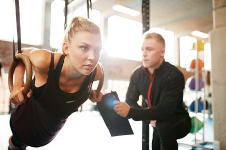 aide à la personne: Fit jeune femme avec son entraîneur personnel dans le gymnase exercice avec des anneaux de gymnastique Banque d'images