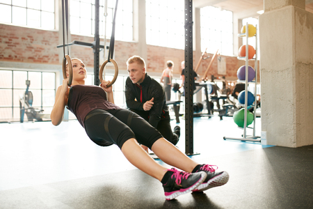 routines: Woman in gym exercising with gymnastic rings being assisted by her personal trainer. Personal trainer helping young woman on her work out routines.