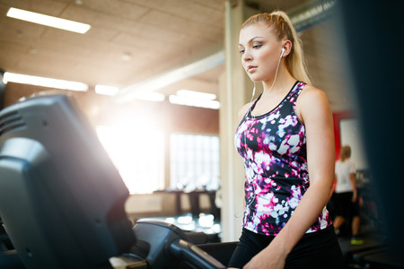 self conscious: Shot of a woman walking on the treadmill at gym. Young focused female exercising at health club, training on exercise equipment.