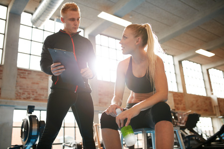 Young woman sitting on a stool and discussing exercise plan with personal trainer. Trainer making an fitness plan for young female client at gym. Standard-Bild