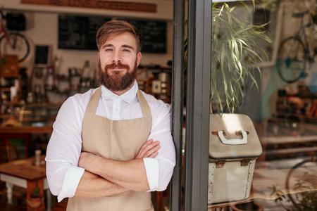 ドアのところに立っているハンサムで自信を持ってカフェのオーナーの肖像画。若者は、笑みを浮かべてカメラを見て腕を組んで立っています。 写真素材