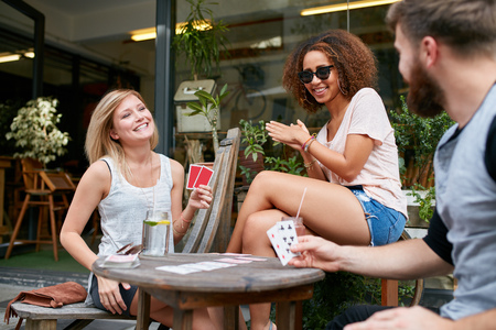 Drie vrienden zitten in openlucht cafe en speelkaarten en plezier maken. Gelukkige jonge mensen op de stoep cafe genieten van het spelen van poker spel.