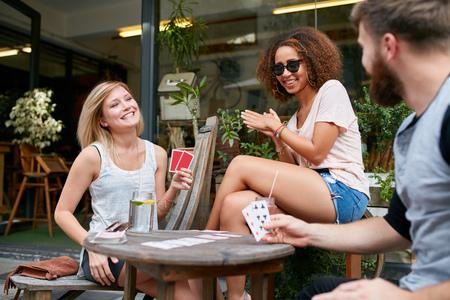 cartas de poker: Tres amigos sentados en el caf� al aire libre y jugando a las cartas y divertirse. Felices los j�venes en la acera cafeter�a disfrutando de juego de juego de p�quer.