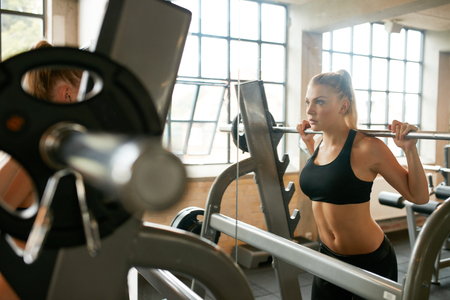 Focused young woman lifting weights in health club. Woman doing squats in front of mirror in gym.