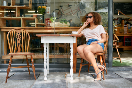Portrait of stylish young woman sitting alone outdoors at sidewalk cafe looking away and thinking. Young african woman sitting at coffee shop.