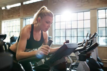 Fit vrouw uit te werken op hometrainer in de sportschool. Indoor shot van een vrouwelijke doet fitness training op het spinnen fiets health club.