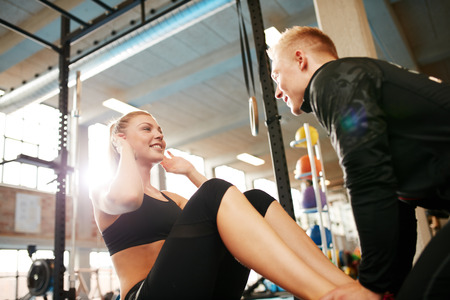 sit ups: Happy athletic woman doing curl up exercise at the gym with the help of her personal trainer. Fitness female doing sit ups with man holding her feet.