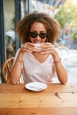 african coffee: Portrait of young african woman drinking coffee at sidewalk cafe. Attractive young girl with curly hair holding a cup of coffee, looking at camera smiling.
