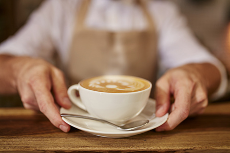 Close up of man serving coffee while standing in coffee shop. Focus on male hands placing a cup of coffee on counter.