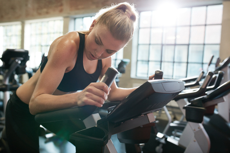 cardio workout: Fitness woman on bicycle doing cardio workout at gym. Fit young female exercising on gym bike.